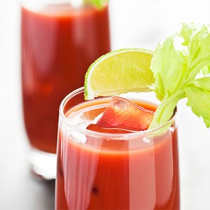 Glass filled with bloody mary mocktail and ice, garnished with a lime wedge and celery stalk