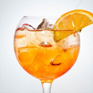 Wine glass filled with ice and orange beverage with orange wedge on rim