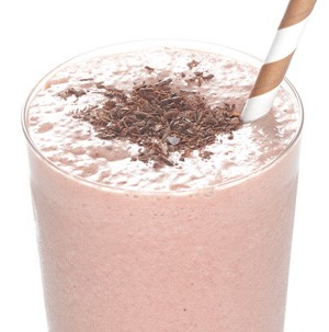 Glass of chocolate-raspberry smoothie garnished with chocolate shavings and straw