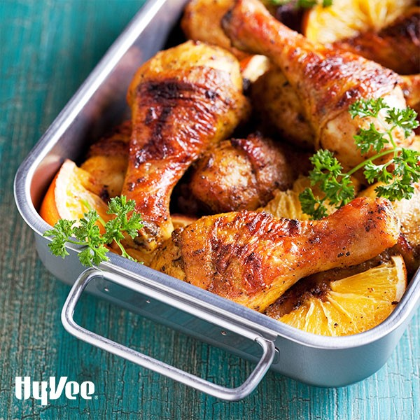 Pan filled with baked lemon chicken drumsticks garnished with baked lemon wedges