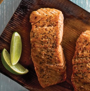Seasoned salmon fillet on a wooden cutting board with lime wedges on side