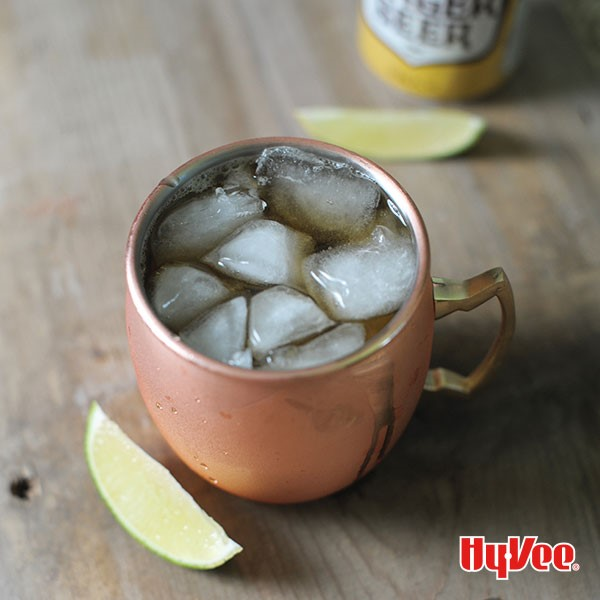 Copper cup filled with mule, ice cubes and lime wedges on the side