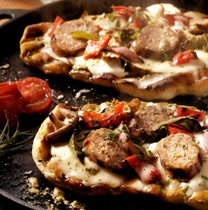 Grilled pizza dough stacked with melted cheese, pesto, and sliced tomatoes and peppers