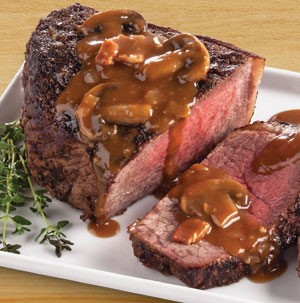 Beef bottom round roast topped with beer and mushroom sauce on a white platter
