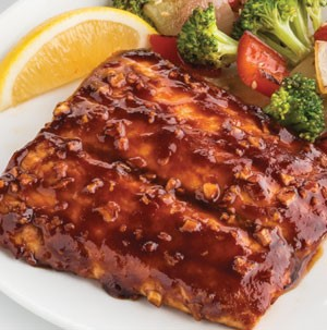 Plate of barbecue-glazed salmon served with vegetables and lemon wedge
