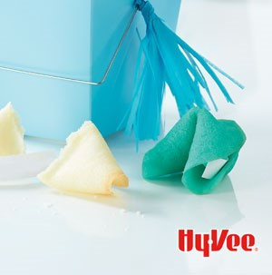 Green and white fortune cookies next to a blue gift box