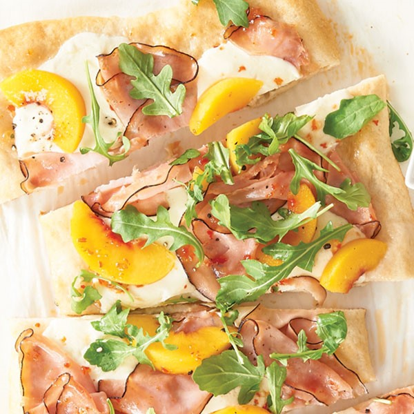 Sliced thin crusted pizza topped with sliced peaches, thinly sliced deli ham, and fresh arugula