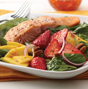 Bed of spinach topped with salmon, strawberries, onions and mangos