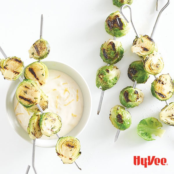Grilled skewered brussels sprout halves over a bowl of lemon aioli