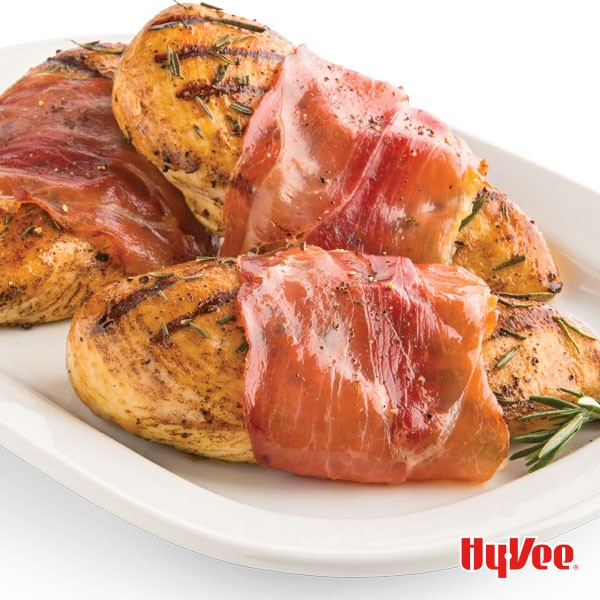 White plate with three prosciutto-wrapped chicken breasts, garnished with rosemary sprigs
