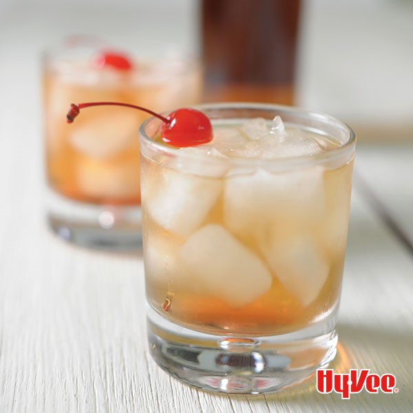 Glasses filled with whisky, ice, and topped with red cherry