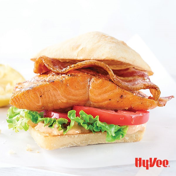 Bun topped with lettuce, sliced red tomatoes, grilled salmon fillet and cooked bacon strip