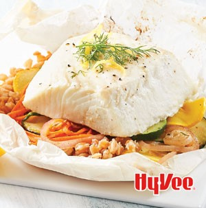 Baked halibut on top of mixed baked vegetables garnished with fresh lemon peel and fresh herbs