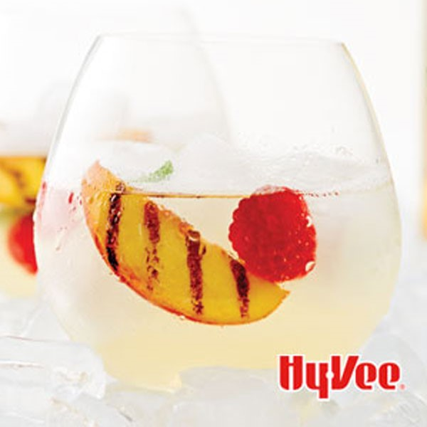 Glass of white sangria garnished with grilled peach slice and a raspberry