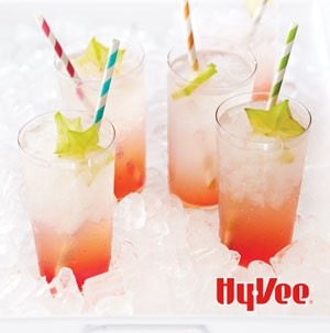 Four glasses of cachaca coolers garnished with starfruit and colored straws