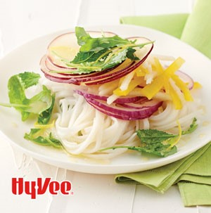 Salad on a bowl with thinly sliced red apples, bell peppers, and mixed greens