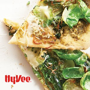 Two overlapping slices of pesto and green veggie pizza, garnished with shredded Parmesan