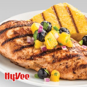 Plate of grilled chicken breast topped with peach blueberry salsa and grilled polenta
