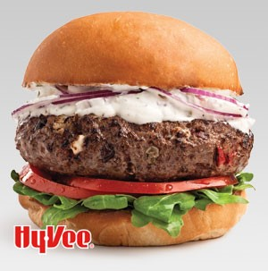 Bun topped with lettuce, tomato slices, burger patty, aioli, sliced red onion and topped with other half of the bun