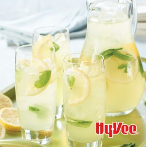 Three glasses of mint lemonade on a try with pitcher with sliced lemon wedges and mint leaves as garnish