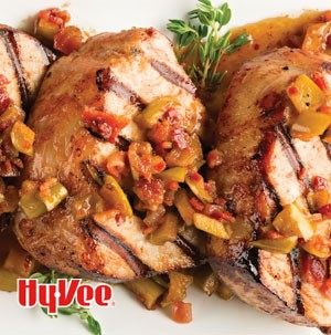 Grilled pork chops topped with apples and bacon bits
