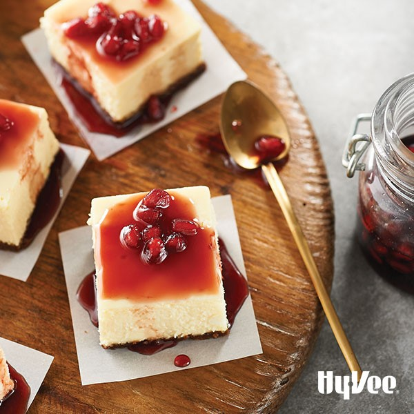Cheesecake squares topped wth pomegranate sauce and seeds on parchment paper