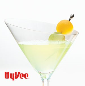 Martini glass filled with drink and two skewered melon balls