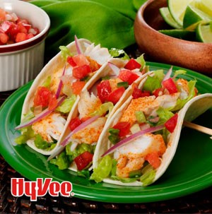 Seasoned white fish in flour tortillas with diced tomatoes, shredded lettuce and sliced red onions
