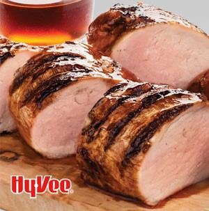 Grilled and sliced pork tenderloin on a wooden cutting board