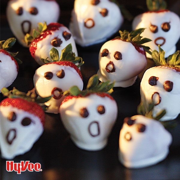Whole strawberries coated in white chocolate and decorated with milk chocolate to look like ghosts