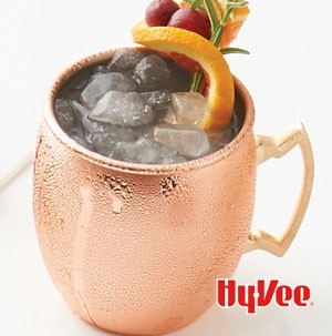Copper glass filled with crushed ice and garnished with orange wedge, fresh cranberries, and fresh rosemary sprig