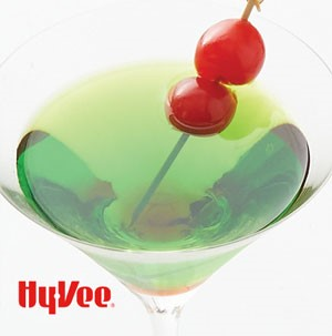 Green martini topped with two cherries on a wooden skewer