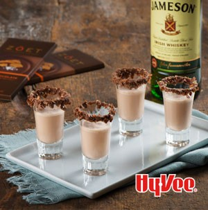Chocolate milkshake shooters on white plate and rimmed with shaved chocolate