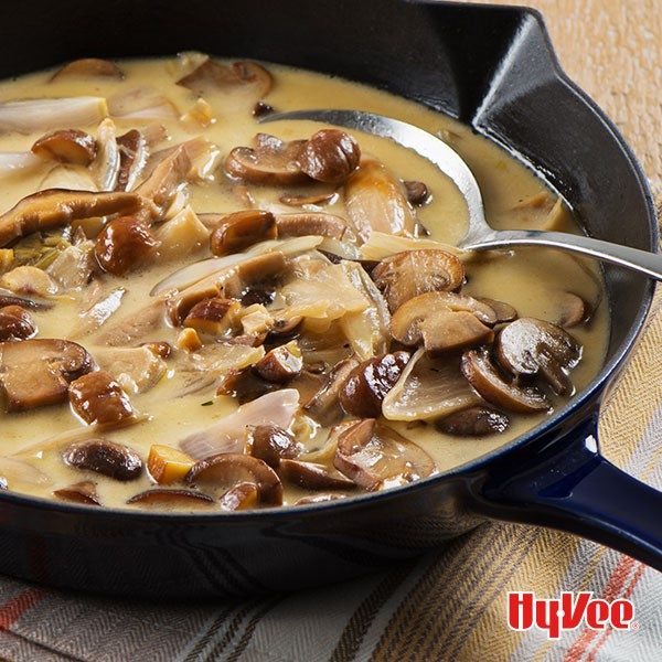 Sliced mushrooms, onions, and gravy in skillet with spoon