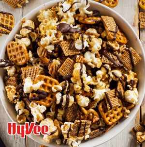 Bowl of mixed popcorn, cereal, pretzel squares and pecans, drizzled in dark chocolate