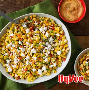 White bowl filled with corn and topped with crumbled white cheese