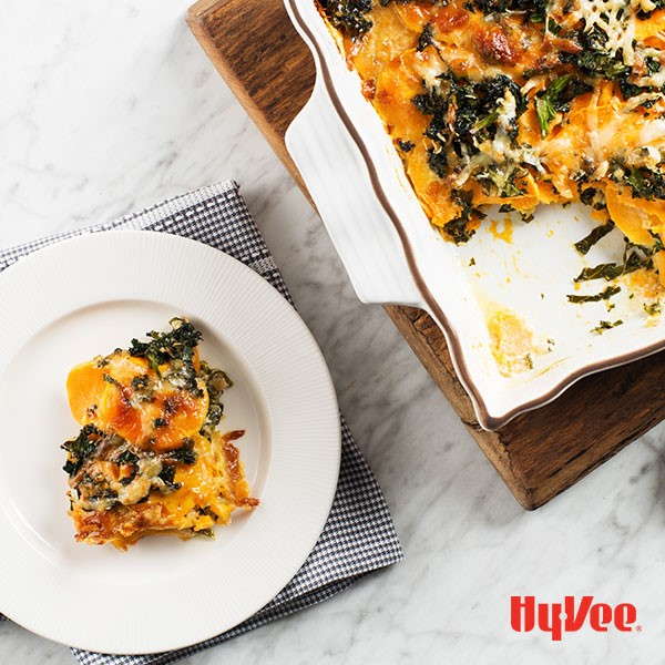 Potato and Kale gratin baked in a casserole dish with piece on a plate