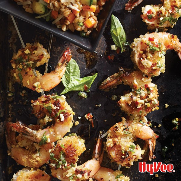 Grilled shrimp skewers garnished with bread crumbs and fresh basil