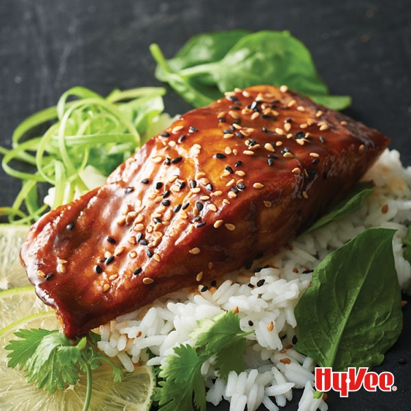 Glazed salmon topped with black sesame seeds over rice garnished with cilantro, lime slices, basil, and green onions