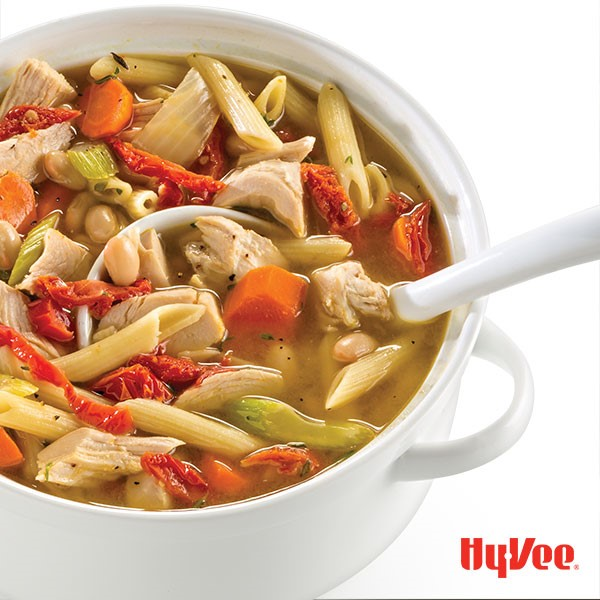 White casserole dish filled with vegetable broth, pasta, turkey, and beans