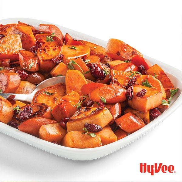 Roasted sweet potatoes with cranberries and garnished with thyme sprigs