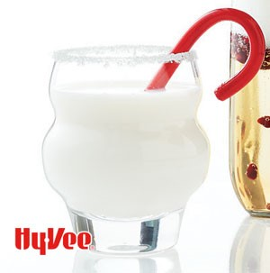 White chocolate beverage in a clear glass with red candycane
