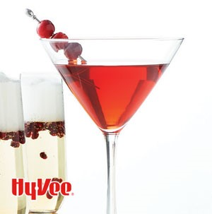 Glass filled with red martini with garnished with cranberries on skewer