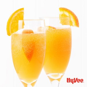 Carbonated orange beverages with orange slices in the drink and on the glass