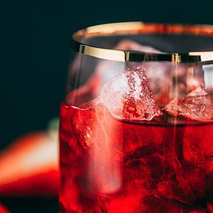 Red juice in a clear glass filled with ice