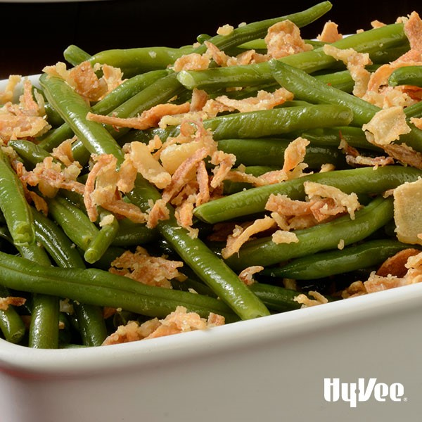 White casserole dish filled with cooked green beans, and crispy onion topping