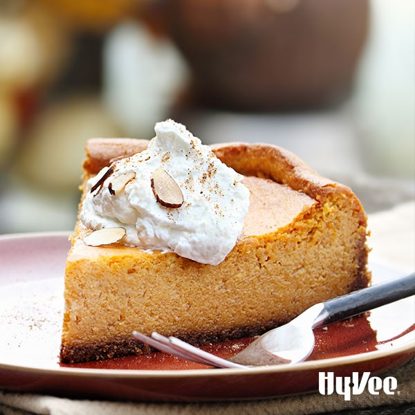 Slice of pumpkin pie on a red plate with a fork and a dollop of whipped topping with sliced almonds