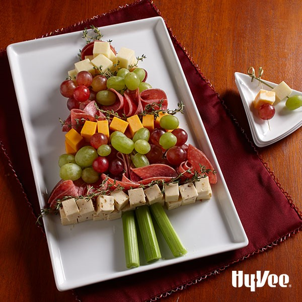 White platter topped with diced cheese cubes, sliced meat, vegetables, and multi colored grapes to make up a Christmas tree