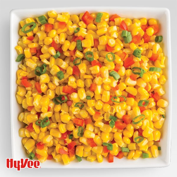Square white dish filled with corn kernels, red peppers and sliced green onions