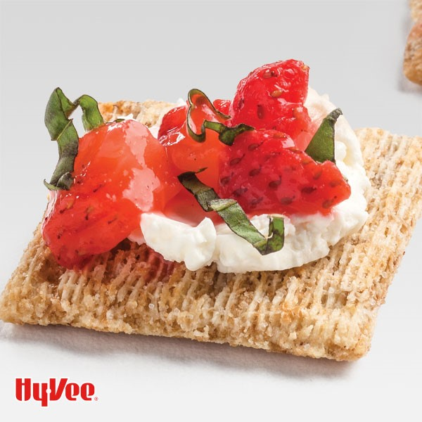 Square cracker topped with cream cheese, strawberries and basil